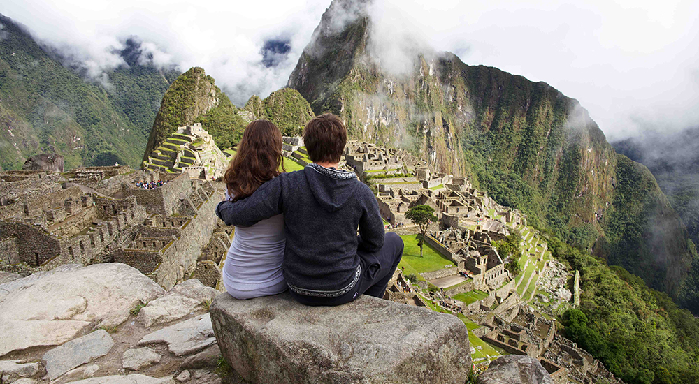 Couple sitting on a rock in front of Machu Picchu